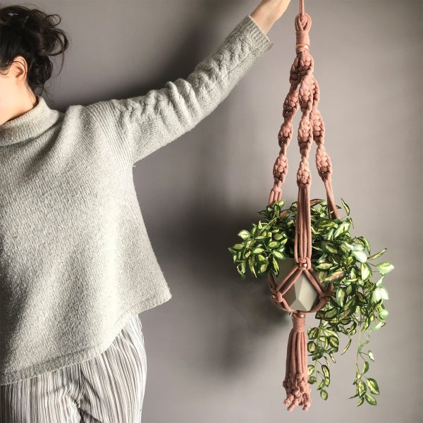 Person holding a chunky cotton copper plant pot hanger