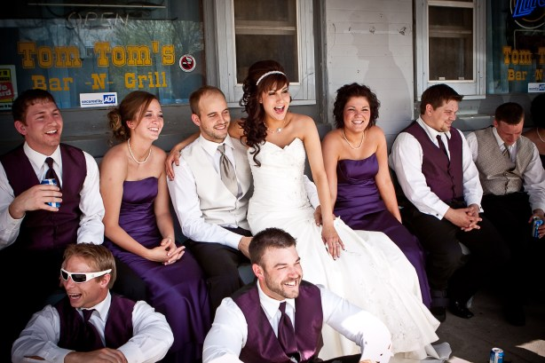Wedding party smiling and laughing outside bar and grill