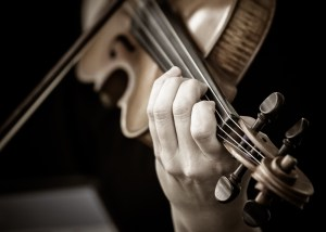 Close up of violinist with fingers on strings