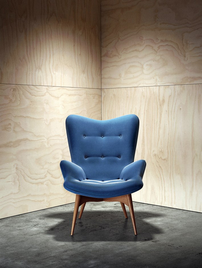 A render showing polished concrete floor, plywood walls and one blue chair