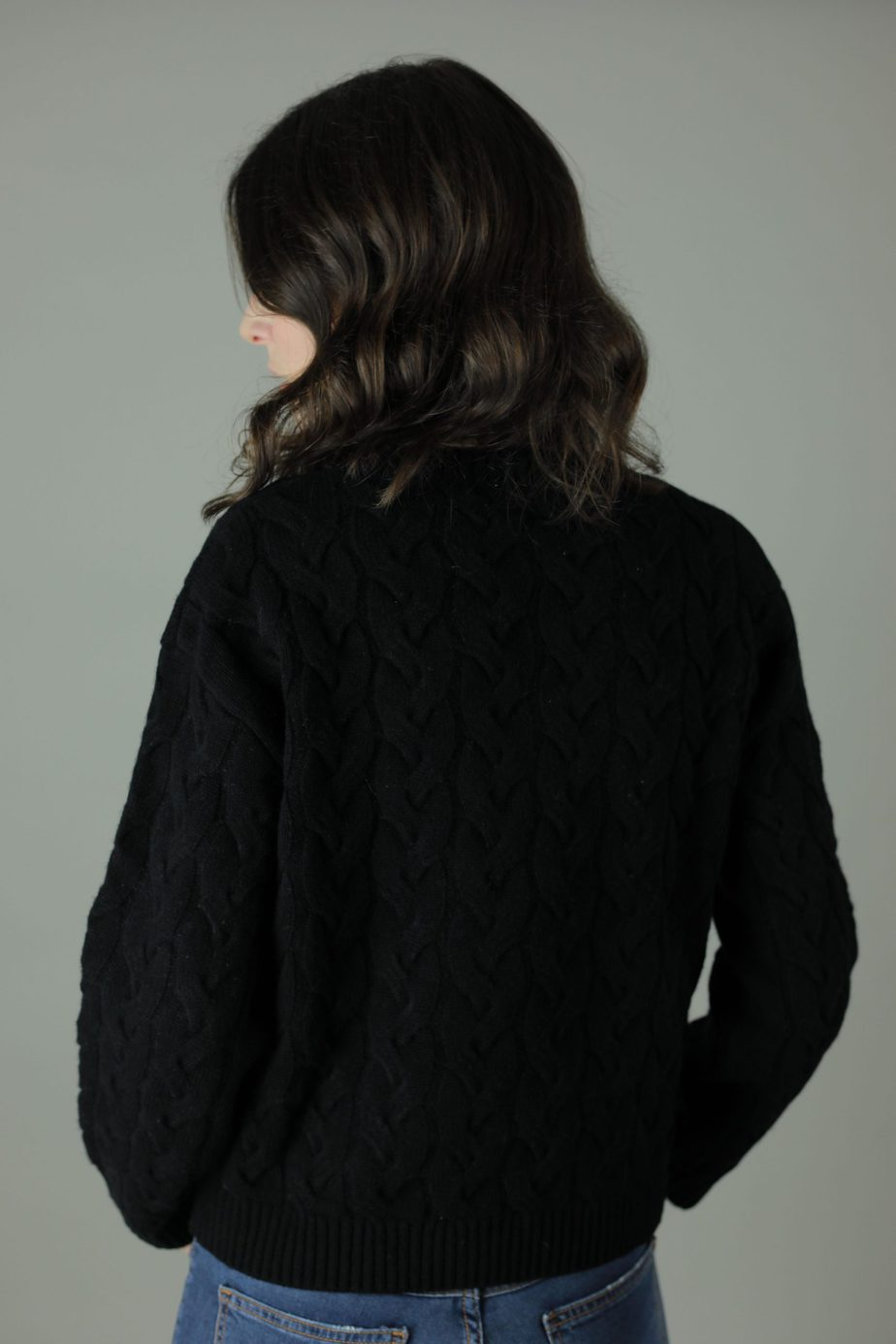 The 100% cashmere Cable-Knit Lana sweater is the luxurious feel you need against your skin this year. Luxuriously woven to give you the perfect look and feel of luxury offered in three different colours with an option of straight edge or scallop edge in our quality cashmere collection. Back view.