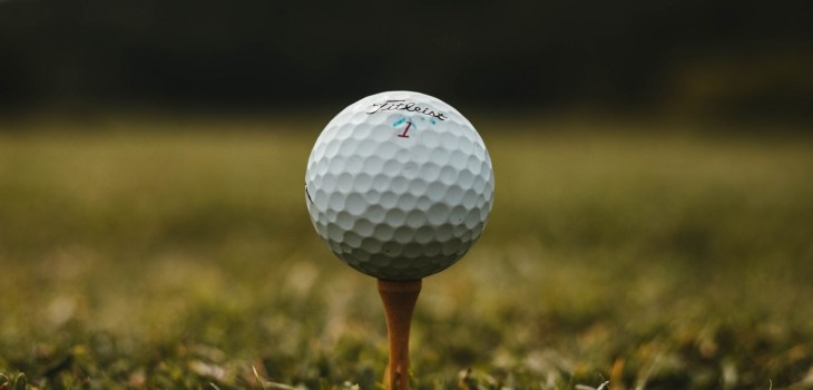 close up of golf ball on tee in grass