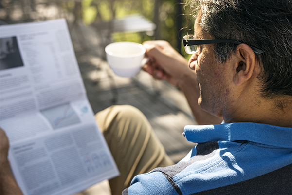 Man wearing glasses and reading the newspaper