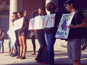 Students stand outside a building holding signs in support of DACA.
