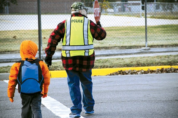 Wes Schmidt, right, helps a student cross the street this fall near Sunset Elementary School.