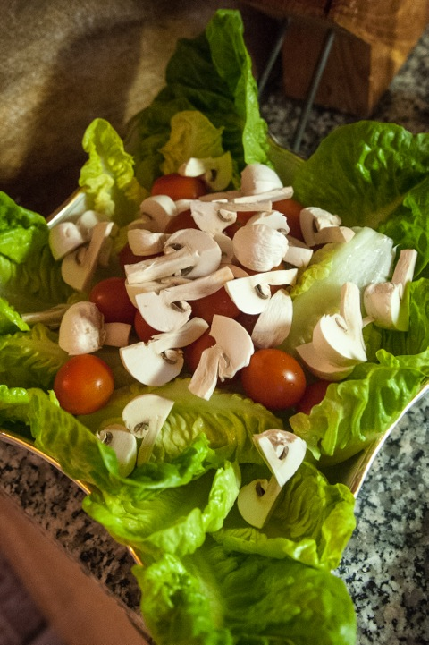 Bild: Die Salatblätter mit einigen rohen Chamignon, Cocktailtomaten und Schinken anrichten.
