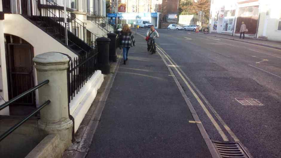 A cyclist riding towards me on the park end pavement, Queens Road, Hastings