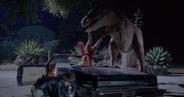 A still image from Tammy and the T-Rex, which shows a Tyrannosaurus Rex lifting a woman out of a convertible car by the ankle.