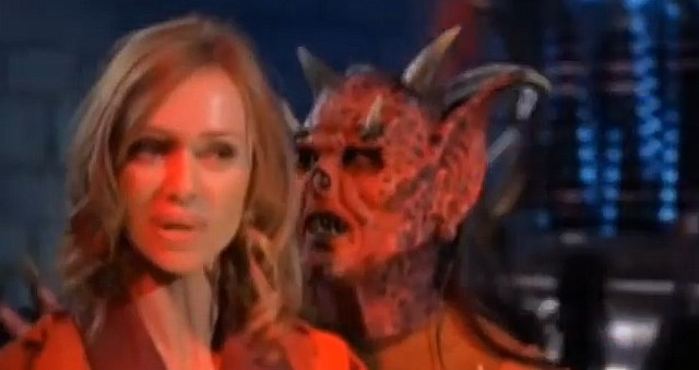 An image of Vanessa Angel as Erica Sharpe and Christopher Bergschneider, appearing in heavy makeup, as Bael in Puppet Master VS Demonic Toys.