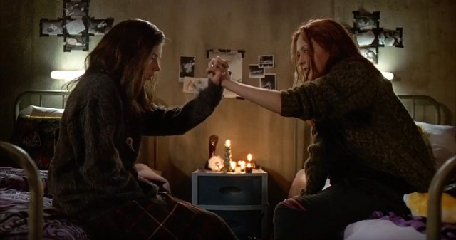 A still image taken from the horror film Ginger Snaps (2000). It shows two young women linking hands.