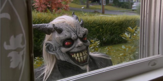 A still shot from the film Satan's Little Helper. It shows a man in an evil-looking devil mask peering in through a house window.