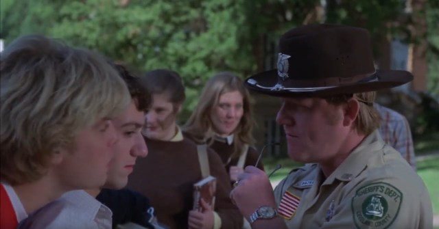 A screenshot from the 1981 horror film Final Exam. It shows a police officer confronting a group of teenagers.