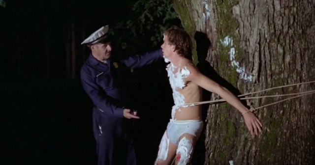 A screenshot from the 1981 horror film Final Exam. It shows an old campus security taunting a naked man who is tied to a tree.