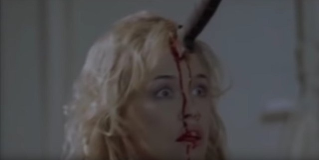A screenshot taken from the 2006 horror-comedy film, Gingerdead Man. It shows a young blonde woman with a knife stuck in her forehead.