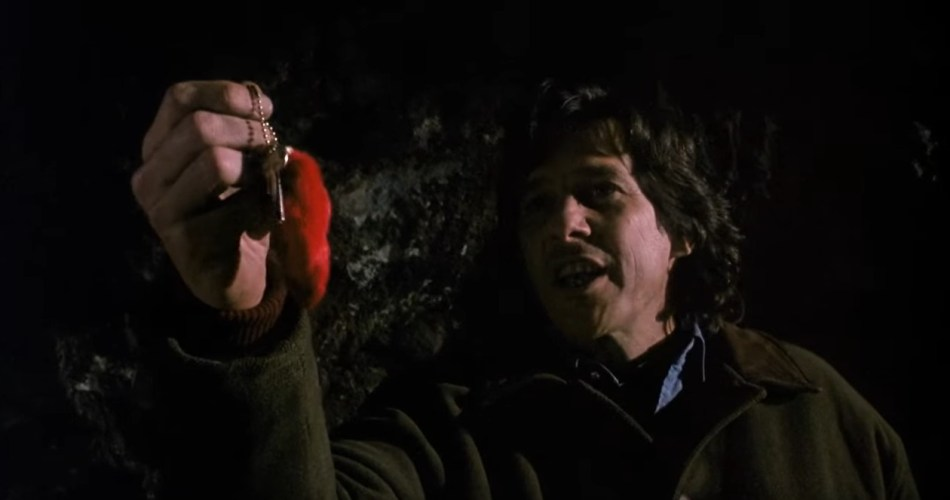 A stll shot taken from the 1991 horror film 'Sometimes They Come Back'. It shows a man holding up a lucky charm.