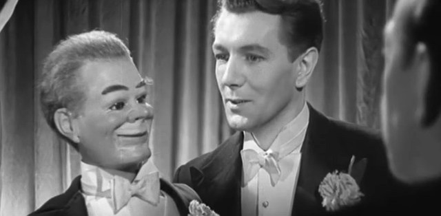 A screen shot taken from the 1945 horror film 'Dead of Night'. It shows a man holding a ventriloquist's dummy.