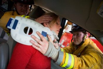Two firemen helping woman with neck brace