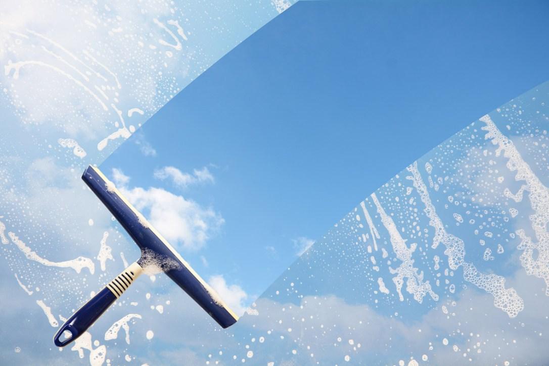 Eine Fensterscheibe, die mit Reinigungsmittel eingeschäumt ist und mit einem Abzieher gereinigt wird.