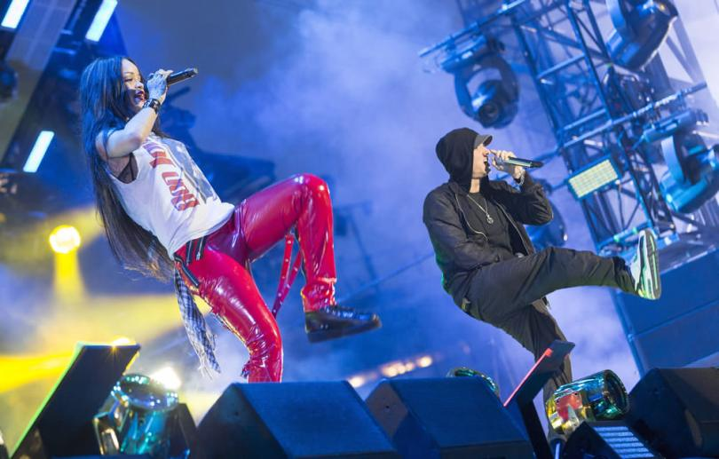 Rihanna performing during The Monster Tour in Detroit wearing a Bon Jovi You Give Love A Bad Name t-shirt, Tripp NYC custom red vinyl bondage pants, Comme des Garcons black high-top sneakers, Fallon classique crystal collar in gunmetal