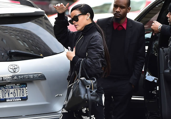 Rihanna wearing Fear of God LA black bomber jacket, Dimepiece Verbage black sweatpants, Manolo Blahnik Chaos sandals, Ray-Ban Wayfarer sunglasses, Balmain Pierre handbag