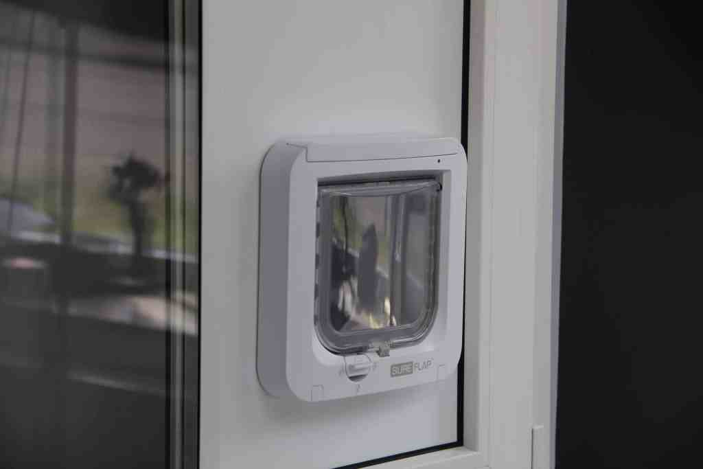 Katzenklappe eingebaut in eine Glasscheibe und Paneel im Fenster