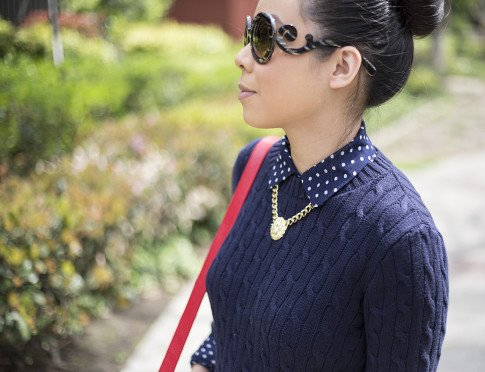 An Dyer wearing Sole Society Britt Messenger Bag in Red, Gold Lion Head Necklace, Navy Polka Dot Blouse, Prada Baroque Sunglasses, American Apparel Navy Cable Knit Pullover