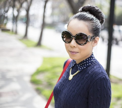 An Dyer wearing Sole Society Britt Messenger Bag in Red, Gold Lion Head Necklace, Navy Polka Dot Blouse, Prada Baroque Sunglasses, American Apparel Navy Cable Knit Sweater