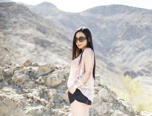 An Dyer wearing  Lovers & Friends Daydream Blouse in Abstract Pastel, Prada Baroque Sunglasses