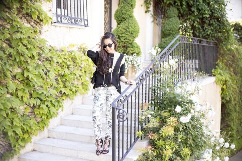 An Dyer wearing Fidelity Denim White Floral Jeans, ShoeMint Romy, ASOS Cross Belt, Rehab Black Sheer Mesh Sweater, Gorjana Griffin Mia Layered Necklace