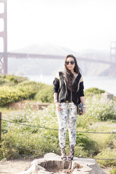 An Dyer wearing Fidelity Denim White Floral Jeans, ShoeMint Romy, ASOS Cross Belt, Rehab Black Sheer Mesh Sweater, Metal Frame Cat Eye Sunglasses, Golden Gate Bridge, Fort Point
