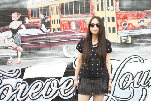 An Dyer wearing Lovers & Friends Kiss Me Top, Zara Leather Fringe Skirt, Olivia & Joy Swanky Straw Satchel, Black Cat Eye Metal Frame Sunglasses