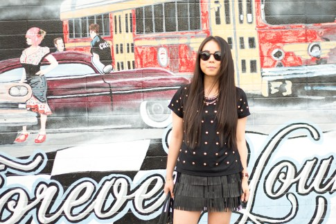 An Dyer wearing Lovers & Friends Kiss Me Top, Zara Leather Fringe Skirt, Olivia & Joy Swanky Straw Satchel, Black Cat Eye Metal Frame Sunglasses