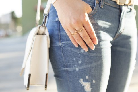 An Dyer wearing WeTheHatters Custom Love More Rings, SoleSociety Elsie White Clutch Bag, Rich & Skinny Ankle Peg Jeans, Hermes Hapi 3mm Bracelet White Leather, Glint & Gleam Dove Grey Belt