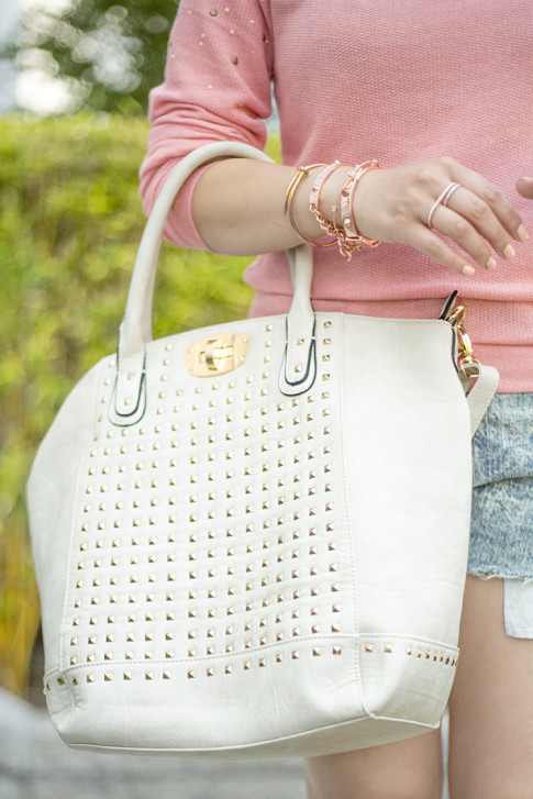 An Dyer wearing Frederick's of Hollywood Cream Studded Tote Bag, Natalie B Rose Gold Double Finger Ring, Glint & Gleam Rose Gold Bracelet Nail Bangles ShopLately