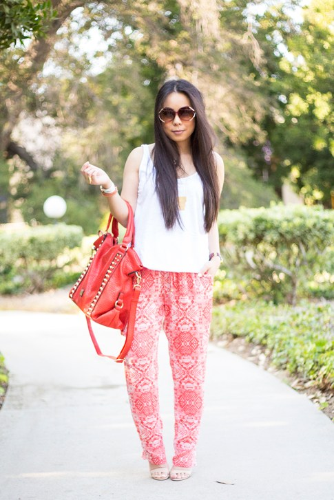 An Dyer wearing Michael Stars Sleeveless Scoop Neck Tank Dress, Chaser Brand Red Tribal Pants, V-Couture by Kooba Ruby Contour Studded Convertible Tote in Coral