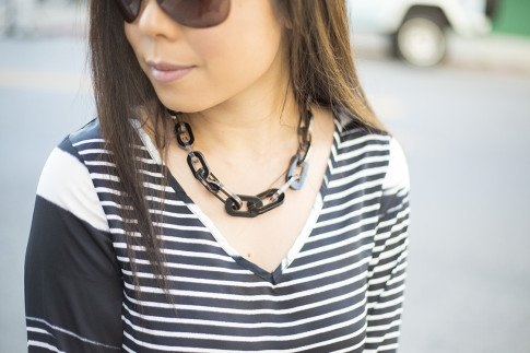 An Dyer wearing Vaunt Sunglasses, JewelMint Shadow Link Necklace, Vintage Havana Striped Top