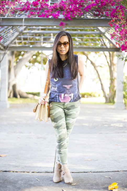 An Dyer wearing Elizabeth & James Lafayette Sunglasses and Glint & Gleam Shifting Shape Necklace ShopLately, Brahmin Atelier Brookline Satchel, CJ by Cookie Johnson Camo Jeans, ShoeMint Milly boots