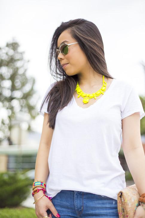 An Dyer wearing ShopLately Glint & Gleam Neon Necklace & multicolor Cork Clutch, Kim & Zozi Bracelets, La mer Collections Watch, Mirrored Sunglasses, Michael Stars White VNeck Tee