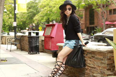 An Dyer wearing Gladiator Sandals, Delikate Rayne Shorts with black fedora panama hat, fisherman sweater