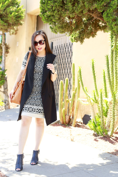 An Dyer wearing Karen Kane dress with Karen Kane Dress and a Ora Delphine Bucket Bag and Express Vest Coata and Louise et Cie Woven Sherree Sandals