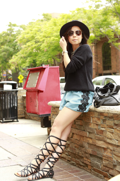 An Dyer wearing Kenneth Cole Gentlesouls Gladiator Sandals, Delikate Rayne Shorts with black fedora panama hat, fisherman sweater