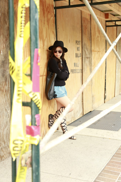 An Dyer wearing MADE eyewear Sunglasses, Gladiator Sandals, Delikate Rayne Shorts with black fedora panama hat