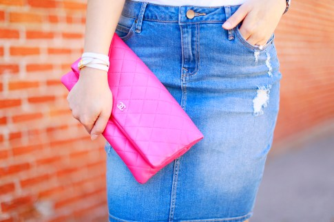 An Dyer wearing Chanel Hot Pink Quilted Foldover Clutch, Hermes Hapi White Leather Wrapped Bracelet, Denim Pencil Skirt, Palter Deliso Bow Pumps