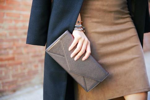 An Dyer carrying Cuyana Bronze Envelope Clutch