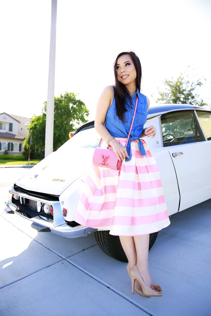 An Dyer wearing Candy Pink Striped Full Midi Skirt and Louis Vuitton Louise Corail, Nude Fluffy Pom Pumps