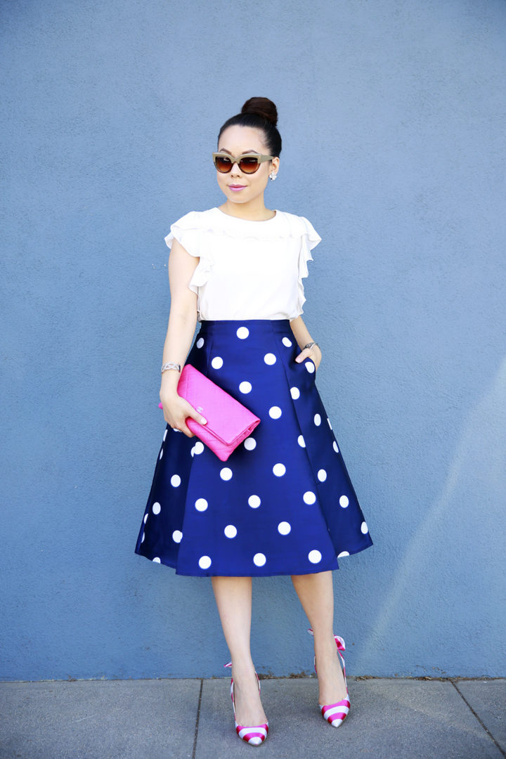 An Dyer wearing Chanel Hot Pink Quilted Foldover Clutch, Amanda Uprichard Ruffled Top with Chicwish Navy Polka Dot Skirt and Pink Striped Bow Pumps