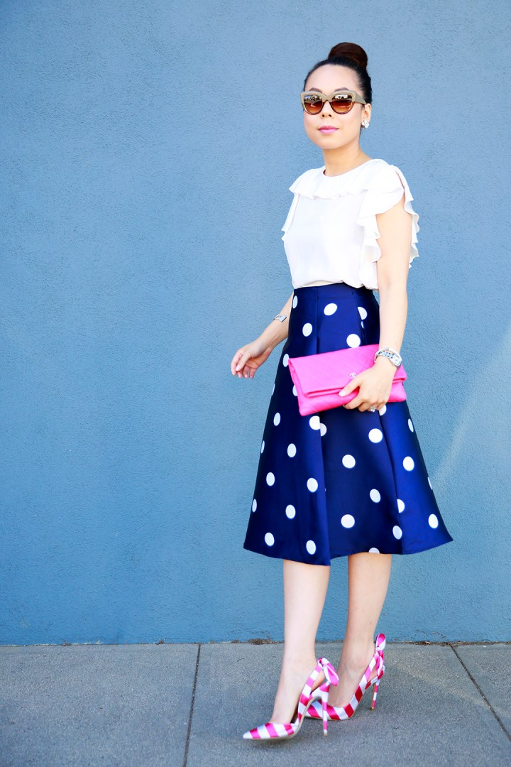 An Dyer wearing Chanel Pink Quilted Foldover Clutch, Amanda Uprichard Ruffled Top with Chicwish Navy Polka Dot Skirt and Pink Striped Bow Pumps