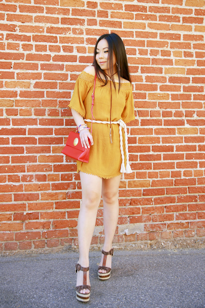 An Dyer wearing mustard yellow off the shoulder dress, rope tie waist belt, chocker necklace, brown platforms