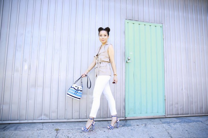 An Dyer wearing Brahming Stripe Bucket Bag, Trench Vest with White jeans and Navy Striped Platform Sandals