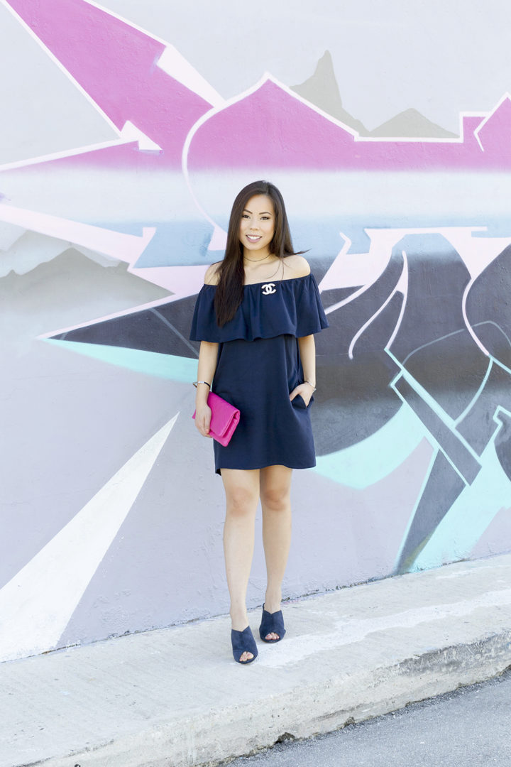 an-dyer-wearing-navy-off-shoulder-dress-with-suede-mules-and-pink-chanel-clutch